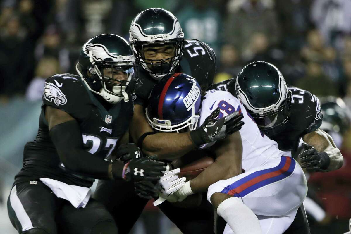 Philadelphia's Malcolm Jenkins (27), Brandon Graham (55) and Nigel Bradham (53) tackle New York Giants' Paul Perkins (28) during the second half.