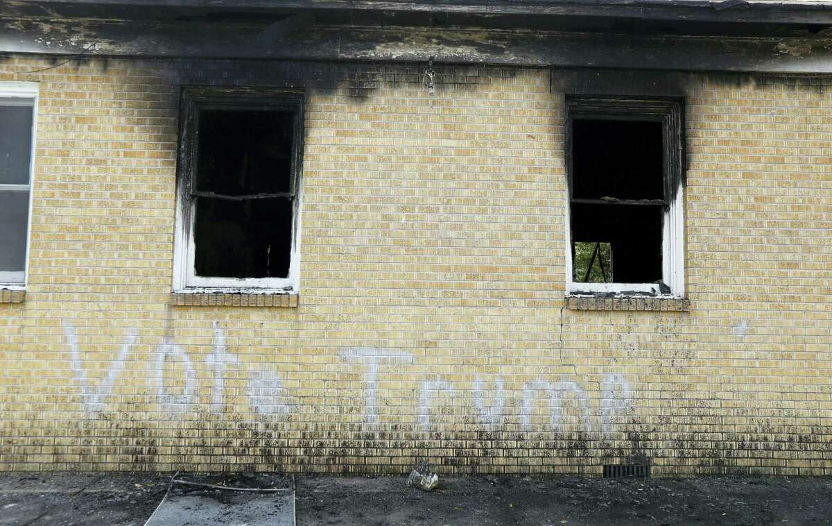 """Vote Trump"" is spray painted on the side of the fire damaged Hopewell M.B. Baptist Church in Greenville, Miss. Mississippi authorities arrested a McClinton Wednesday in the burning of an African-American church that was also spray-painted with the words ""Vote Trump."""