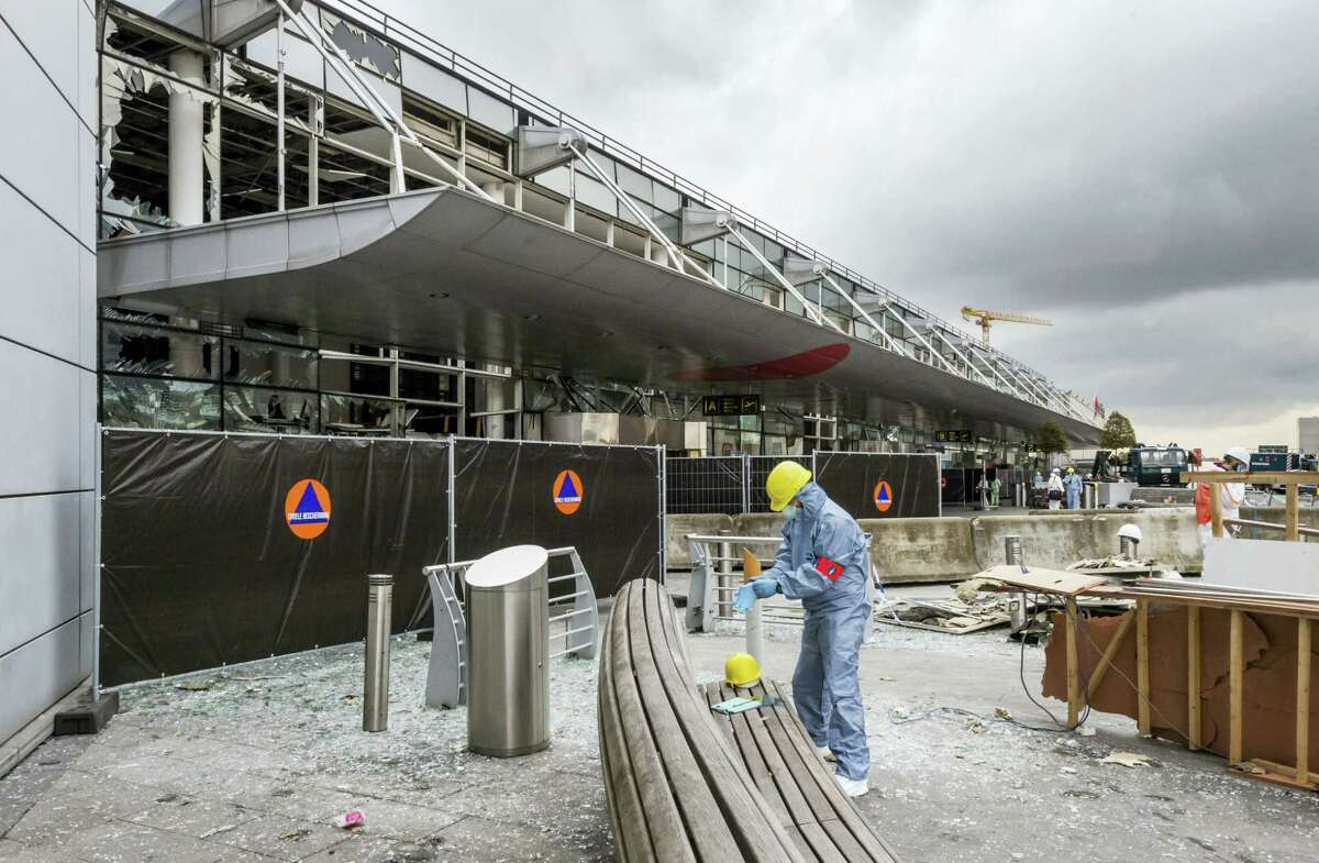 In this March 23, 2016 file photo, a forensics officer works in front of the damaged Zaventem Airport terminal in Brussels. It's unclear when the Brussels Airport will reopen, even after a meeting Friday, April 1 by Prime Minister Charles Michel and key members of the government.