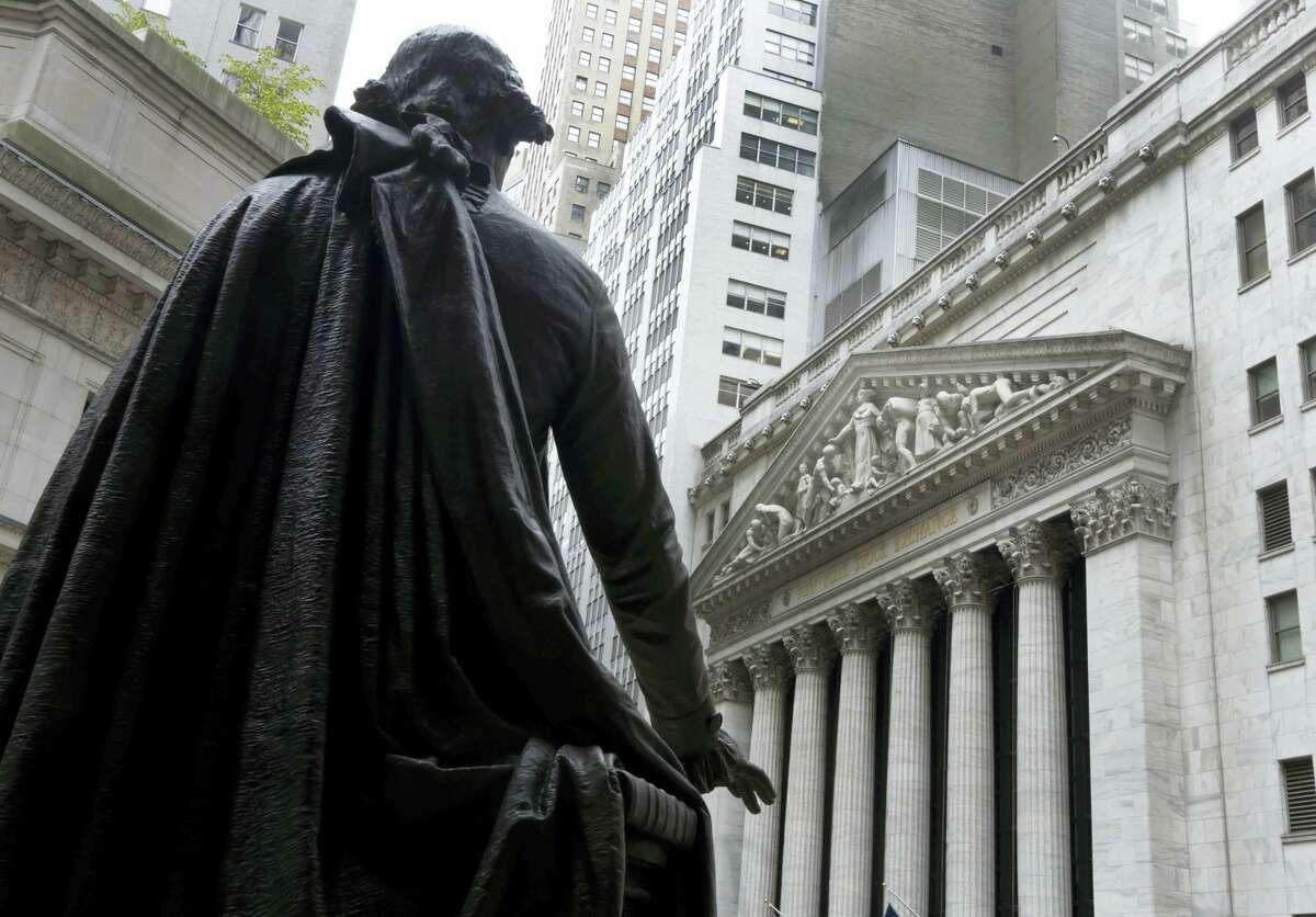 FILE - In this Oct. 2, 2014, file photo, the statue of George Washington on the steps of Federal Hall faces the facade of the New York Stock Exchange. U.S. stocks are sinking with the price of oil and precious metals Friday, April 1, 2016. Energy and mining companies are taking the biggest losses. Global stocks are also falling. Hotel operators Starwood and Marriott are sliding after Anbang Insurance, the Chinese company that sought to buy Starwood, walked away from its offer.