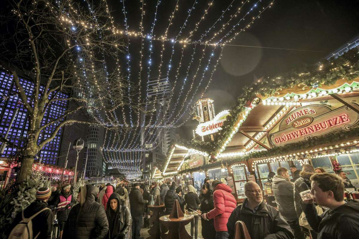 Visitors walk through the re-opened Christmas market on Breitscheidplatz Square in Berlin, Thursday Dec. 22, 2016. Following the attack on the Berlin Christmas market with a truck on Monday that left some dead and more injured, the police are searching for the suspect.