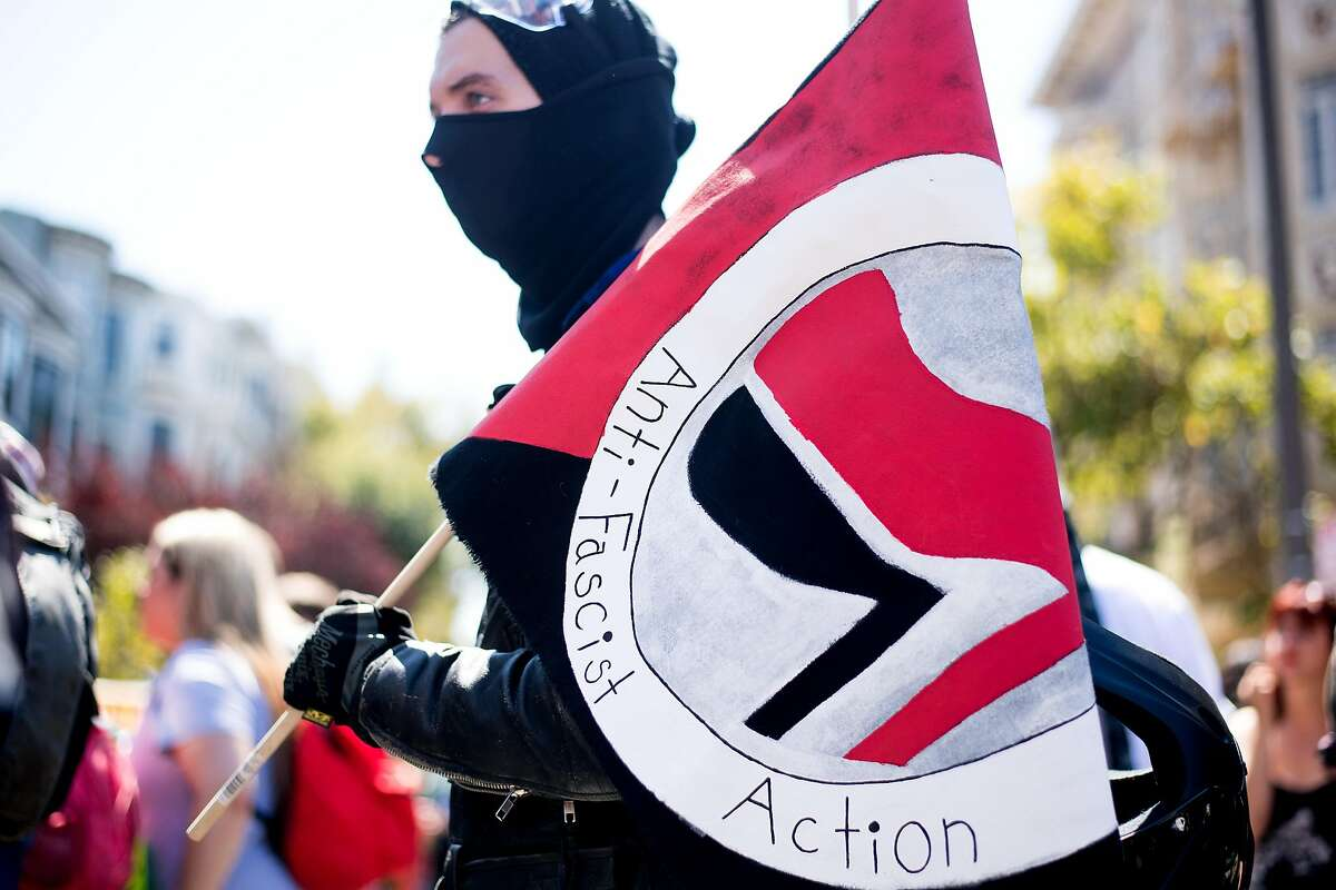 A protester, who declined to give a name, holds an Antifa flag while rallying against a planned conservative gathering on Saturday, Aug. 27, 2017, in San Francisco.