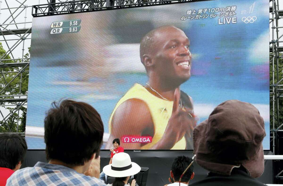 People watch Jamaica's Usain Bolt flash the number one sign just after finishing the men's 100-meter final at the 2016 Summer Olympics held in Rio de Janeiro, on a huge screen during public viewing at Ueno Park in Tokyo, Monday, Aug. 15, 2016. Bolt became the first person to win three straight Olympic 100-meter titles.