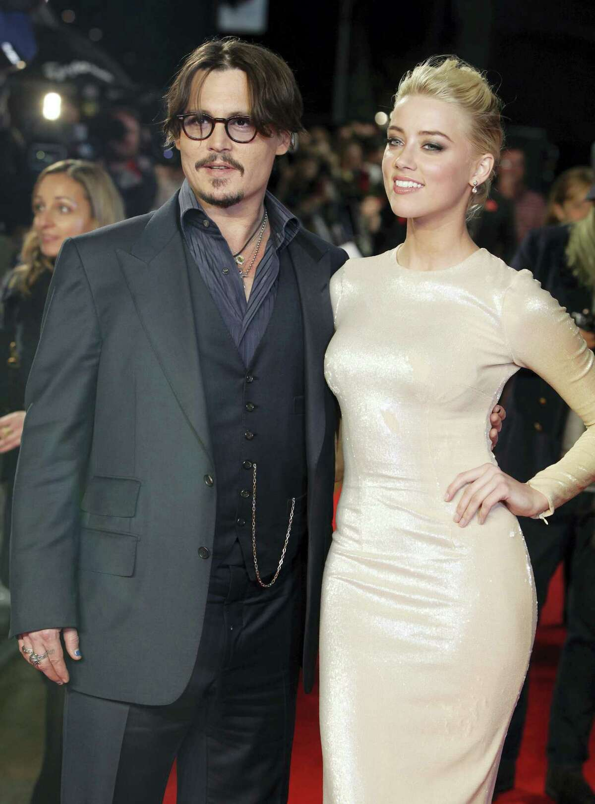 """In this Nov. 3, 2011, file photo, U.S. actors Johnny Depp, left, and Amber Heard arrive for the European premiere of their film, """"The Rum Diary,"""" in London. Heard is withdrawing allegations that Depp physically abused her and has settled her divorce case with the Oscar-nominated actor. Heard filed for divorce in May and days later obtained a temporary restraining order accusing the """"Pirates of the Caribbean"""" star of hitting her during a fight in their Los Angeles apartment in May. Depp denied he abused her, and police said they found no evidence of a crime."""