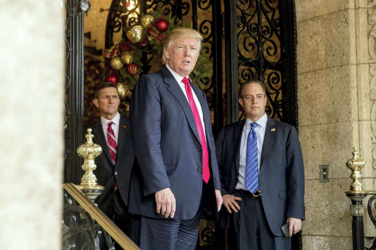 President-elect Donald Trump, center, accompanied by Trump Chief of Staff Reince Priebus, right, and Retired Gen. Michael Flynn, a senior adviser to Trump, left, takes a question from a member of the media at Mar-a-Lago, in Palm Beach, Fla., Wednesday.