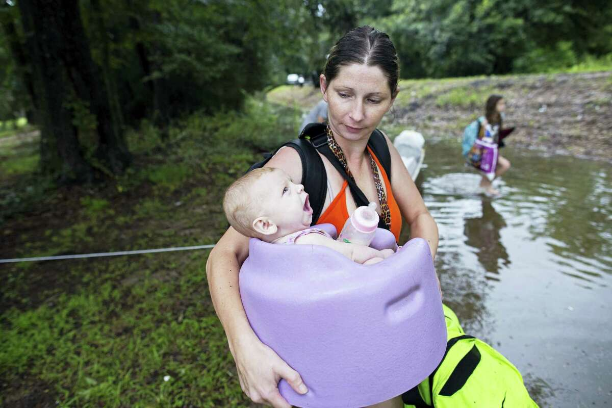 Danielle Blount carries her 3-month-old baby, Ember, to a truck from the Louisiana Army National Guard as they evacuate the area near Walker, La., after heavy rains inundated the region, Sunday, Aug. 14, 2016.