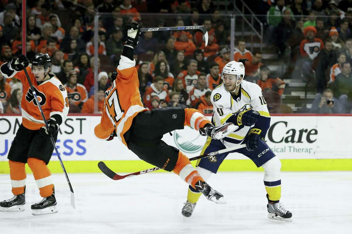 Philadelphia Flyers' Andrew MacDonald (47) is sent flying after a hit from Nashville Predators' Colton Sissons (10) during the third period of an NHL hockey game Monday, Dec. 19, 2016 in Philadelphia.