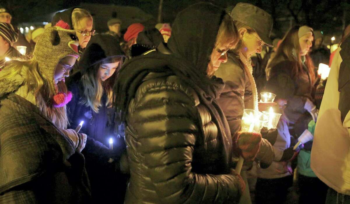 In this Jan. 29, 2016 photo, people hold candles in memory of the three deceased Sheboygan Falls children at River Park in Sheboygan Falls, Wis. Natalie Renee Martin, 11, Carter Maki, 7, and Benjamin Martin, 10, died in a house fire Jan. 26. Natalie, who died saving the lives of even younger children, is among 21 people being honored with Carnegie medals for heroism. The Carnegie Hero Fund Commission, based in Pittsburgh, announced the winners Tuesday, Dec. 20, 2016.