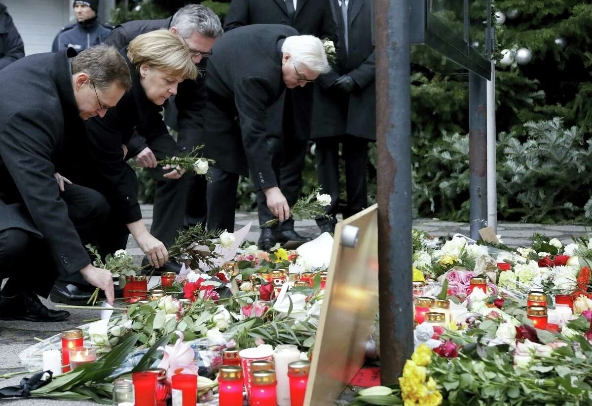 From left, the Mayor of Berlin Michael Mueller, German Chancellor Angela Merkel, German Interior Minister Thomas de Maiziere and German Foreign Minister Frank-Walter Steinmeier attend a flower ceremony at the Kaiser-Wilhelm-Gedaechniskirche in Berlin, Germany, Tuesday, Dec. 20, 2016 the day after a truck ran into a crowded Christmas market and killed several people.