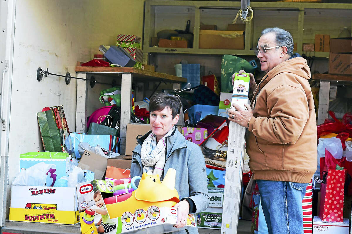 Lynn Robotham, left, and Lenny Byram of O&G are pictured delivering toys to the Torrington Area Youth Service Bureau.