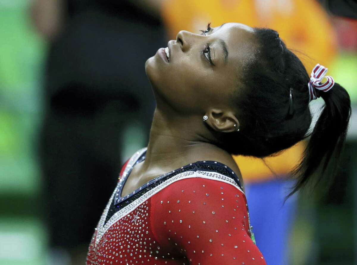 Simone Biles looks at the scoreboard after her balance beam routine.