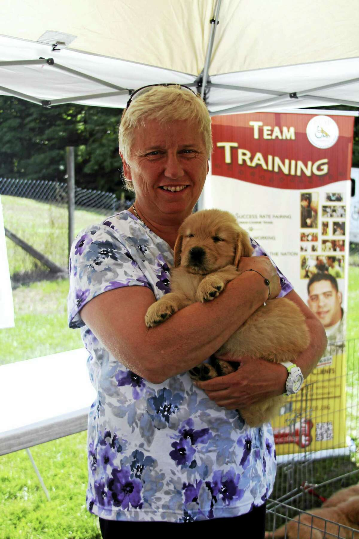 Photos by Erica Kasper Winsted Mayor Candy Perez holds seven week old puppy and future service dog at a recent ECAD presentation on its Laura J. Niles Campus.
