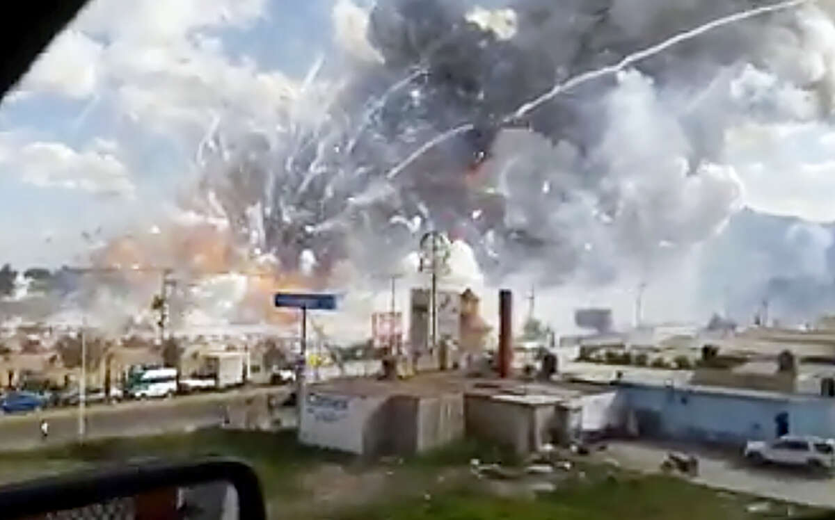 This image made from video shows an explosion ripping through the San Pablito fireworks' market in Tultepec, Mexico, Tuesday, Dec. 20, 2016. Sirens wailed and a heavy scent of gunpowder lingered in the air after the afternoon blast at the market, where most of the fireworks stalls were completely leveled. According to the Mexico state prosecutor there are at least 26 dead.