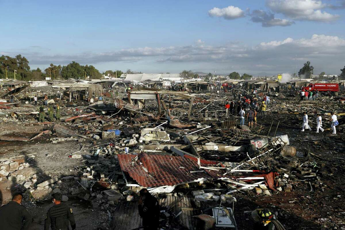 Firefighters and rescue workers walk through the scorched ground of the open-air San Pablito fireworks market, in Tultepec, outskirts of Mexico City, Mexico, Tuesday, Dec. 20, 2016. An explosion ripped through Mexico's best-known fireworks market on the northern outskirts of the capital Tuesday, injuring scores and killing at least 9 people, according to Mexican Federal Police.