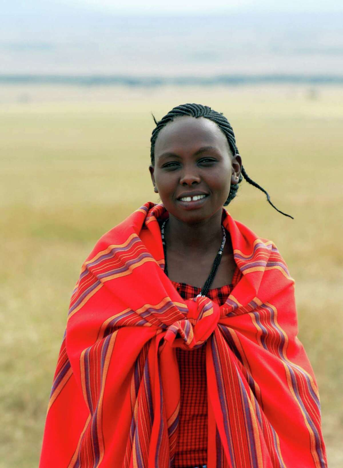 This March 7, 2016 photo shows Judy Koya, a member of Kenya's Maasai tribe on a training mission in Kenya's Maasai Mara region. The Maasai group was participating in a program to brush up on their skills as safari guides. The program also allows tourists to learn alongside them so that the visitors are not just riding along for photo opportunities, but are instead actively learning to tune into the sights and sounds of the natural world. (Charmaine Noronha via AP)