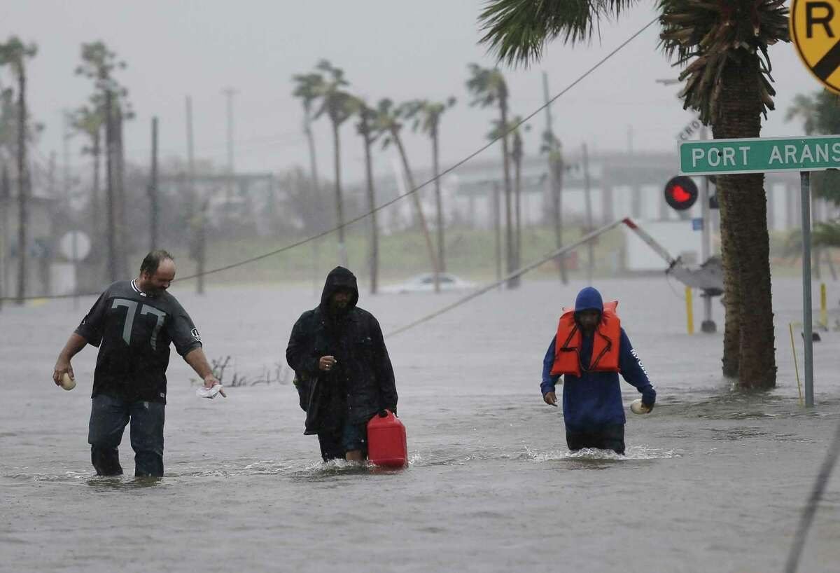 Click through the slideshow to view damage from Hurricane Harvey in the areas surrounding Port Aransas, Aransas Pass and Corpus Christi in South Texas. Rodney Helms (from left), Phil Reynolds and Richard Nino walk in knee-high flood waters to check on Reynolds' boat in Aransas Pass in the aftermath of Hurricane Harvey on Saturday, Aug. 26, 2017. (Kin Man Hui/San Antonio Express-News)