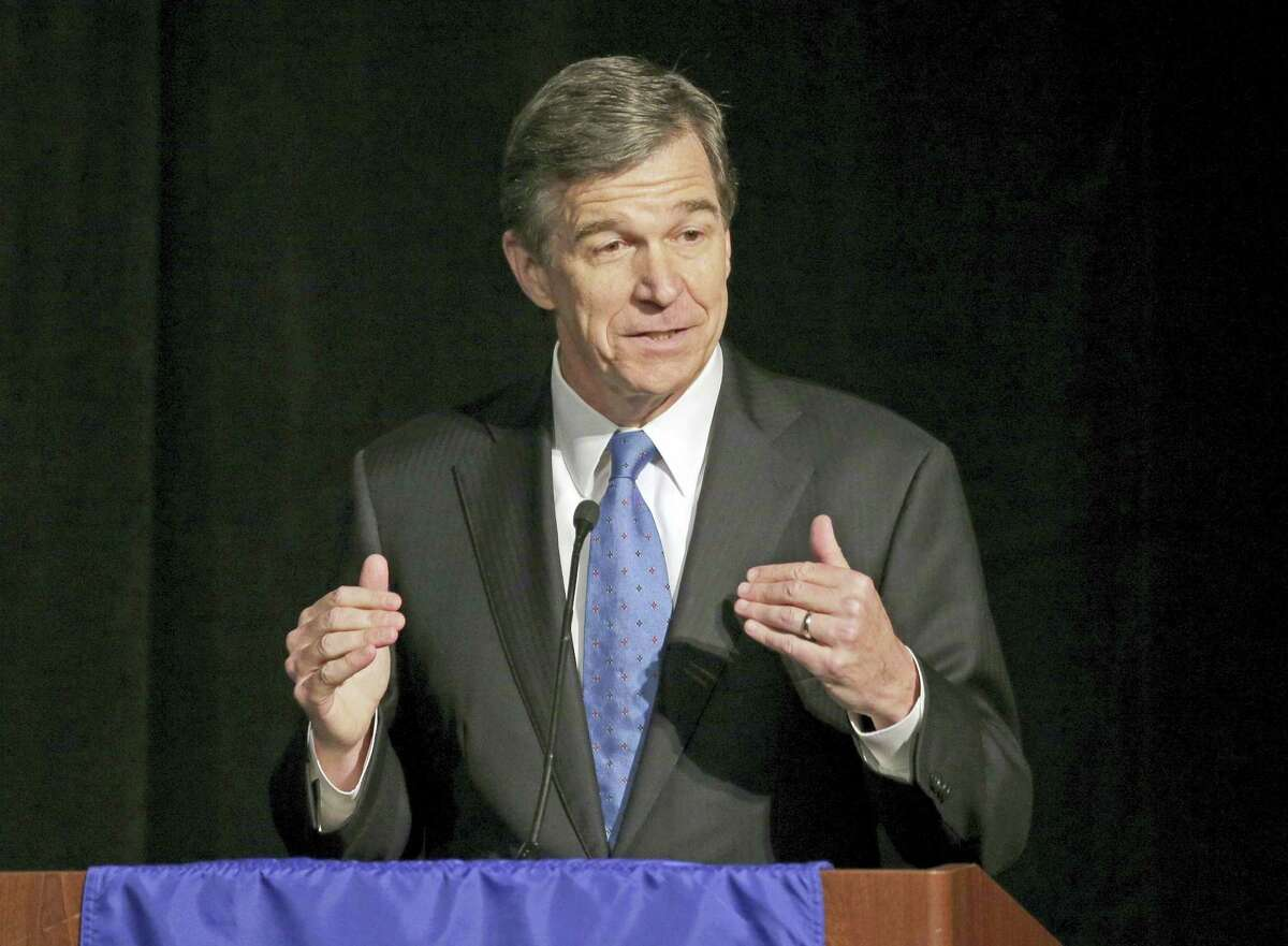 In this June 24, 2016 photo, then-North Carolina Attorney General Roy Cooper speaks during a forum in Charlotte, N.C. Roy, the state's incoming governor, said Monday, Dec. 19, 2016 that North Carolina legislators will repeal the contentious HB2 law that limited protections for LGBT people and led to an economic backlash.