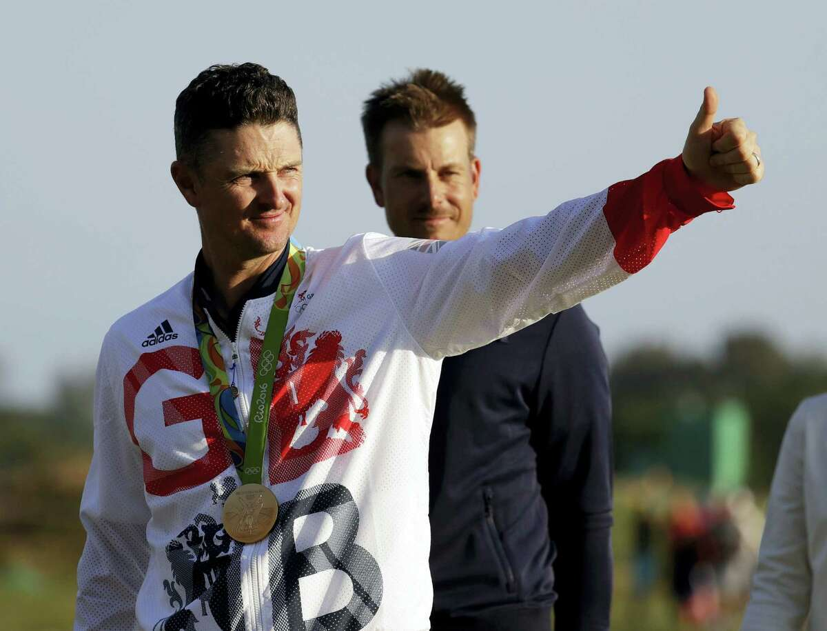 Justin Rose walks up to the medal ceremony with silver medalist Henrik Stenson behind him after the final round of the men's golf event in Rio on Sunday.