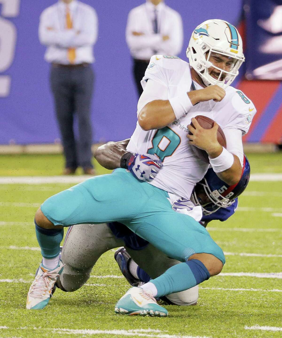 Dolphins quarterback Matt Moore is sacked by Giants defensive end Owa Odighizuwa during Friday's preseason game.