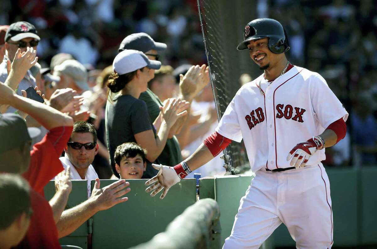 Mookie Betts, right, is welcomed to the dugout after hitting a three-run home run in the fifth inning on Sunday.