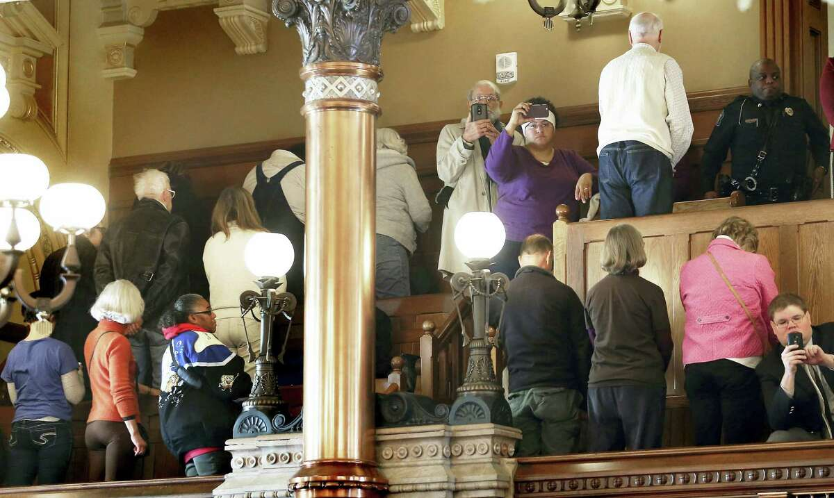 People turn their backs on Electoral College members Monday at the state Capitol as they vote in Topeka, Kan. Kansas' six Republican members of the Electoral College have cast their ballots for President-elect Donald Trump, keeping with the state's popular vote.
