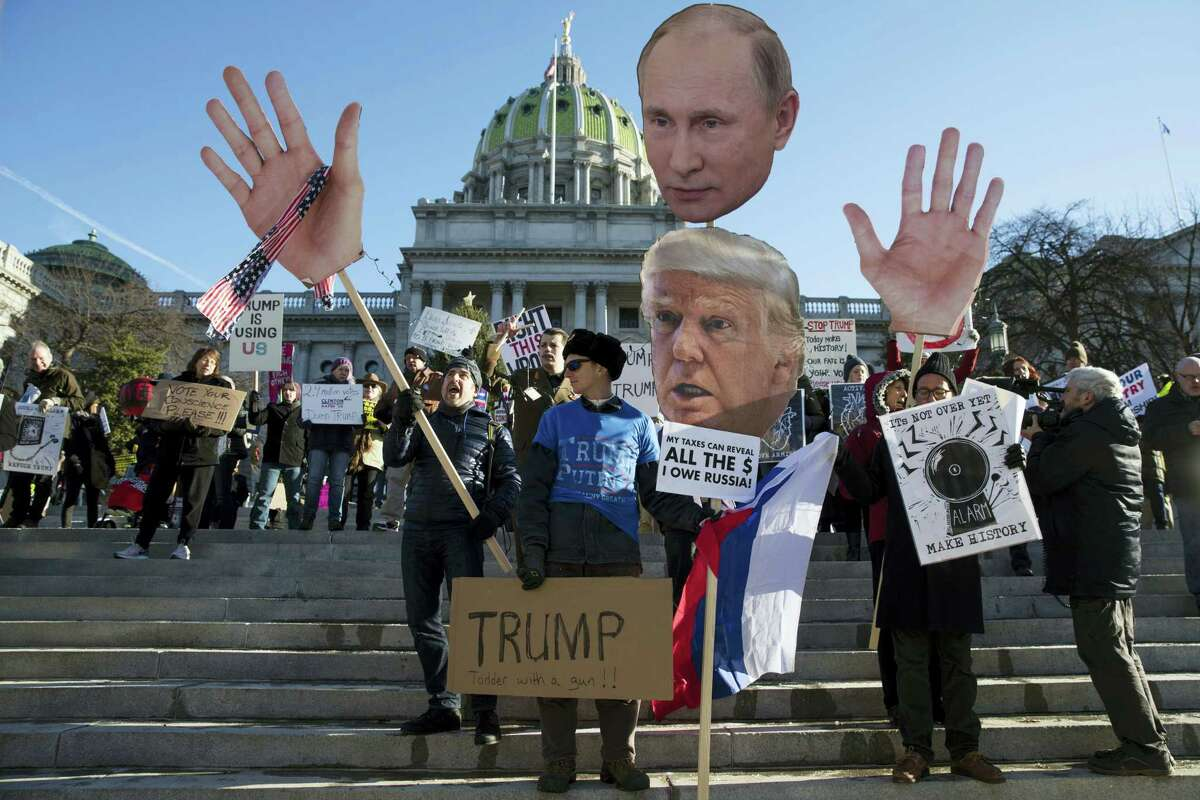Protesters demonstrate ahead of Pennsylvania's 58th Electoral College at the state Capitol in Harrisburg, Pa., Monday, Dec. 19, 2016. The demonstrators were waving signs and chanting in freezing temperatures Monday morning as delegates began arriving at the state Capitol to cast the state's electoral votes for president. (AP Photo/Matt Rourke)