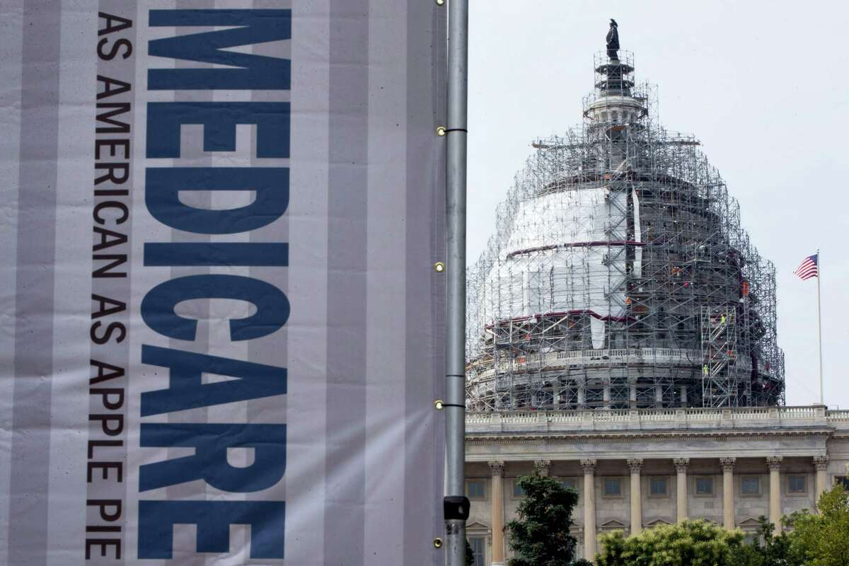 In this July 30, 2015 photo, a sign supporting Medicare is seen on Capitol Hill in Washington. A government report says Medicare beneficiaries can end up with higher hospital bills for some medical services as outpatients than as inpatients.