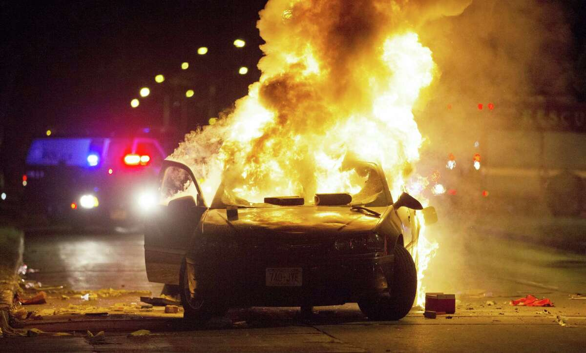 A car burns as a crowd of more than 100 people gathers following the fatal shooting of a man in Milwaukee on Aug. 13, 2016. The Milwaukee Journal Sentinel reported that officers got in their cars to leave at one point, and some in the crowd started smashing a squad car's window, and another vehicle, pictured, was set on fire.