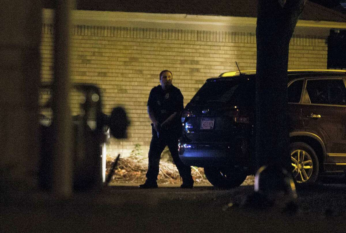 A police officer hides behind a car as a crowd of more than 100 people gathers following the fatal shooting of a man in Milwaukee, Saturday, Aug. 13, 2016. The Milwaukee Journal Sentinel reported that officers got in their cars to leave at one point, and some in the crowd started smashing a squad car's window, and another vehicle was set on fire. The gathering occurred in the neighborhood where a Milwaukee officer shot and killed a man police say was armed hours earlier during a foot chase. (Calvin Mattheis/Milwaukee Journal-Sentinel via AP)