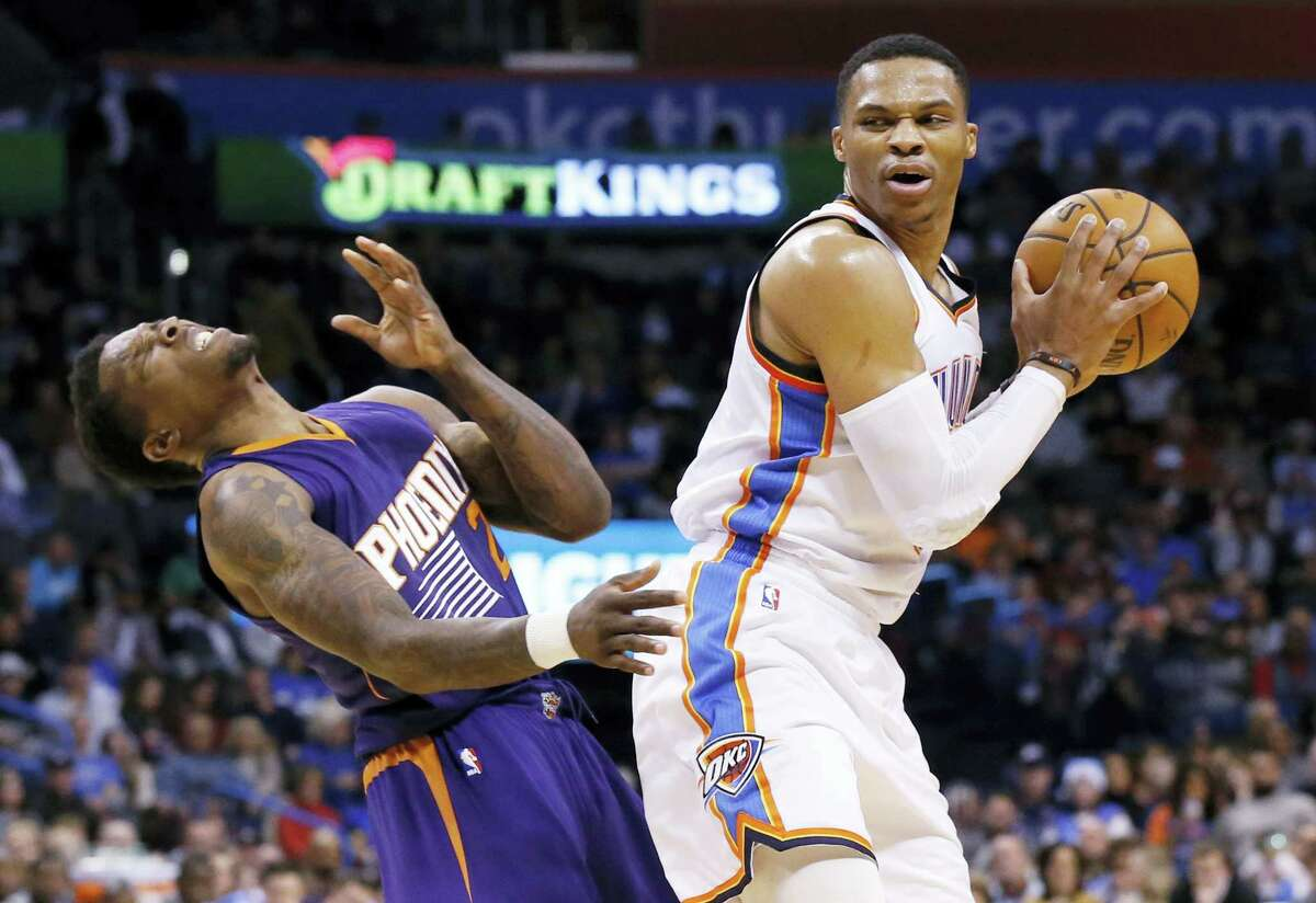 Phoenix Suns guard Eric Bledsoe, left, falls backwards following an offensive foul by Oklahoma City Thunder guard Russell Westbrook, right, in the second quarter of an NBA basketball game in Oklahoma City on Saturday, Dec. 17, 2016.