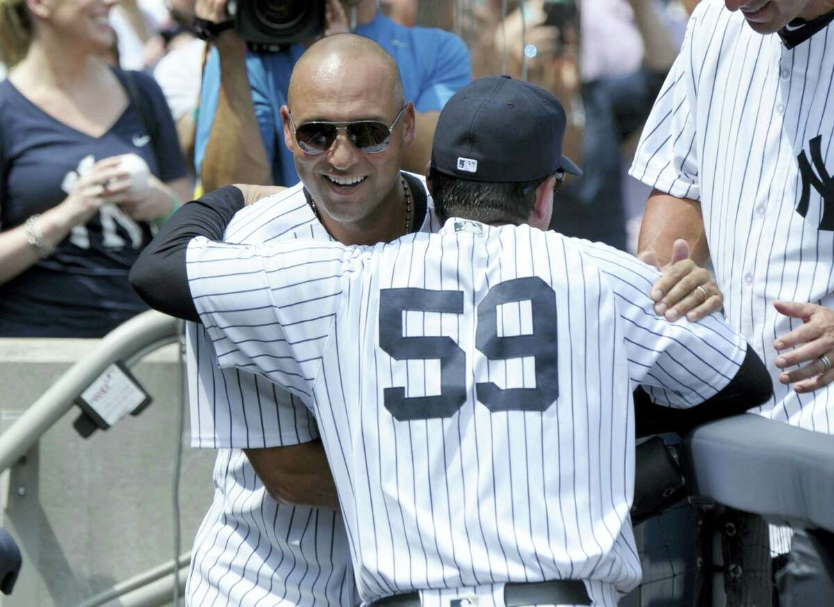 Former Yankees shortstop Derek Jeter hugs bench coach Rob Thompson before a Saturday's game at Yankee Stadium in New York. The 1996 Yankees team was honored before the game.