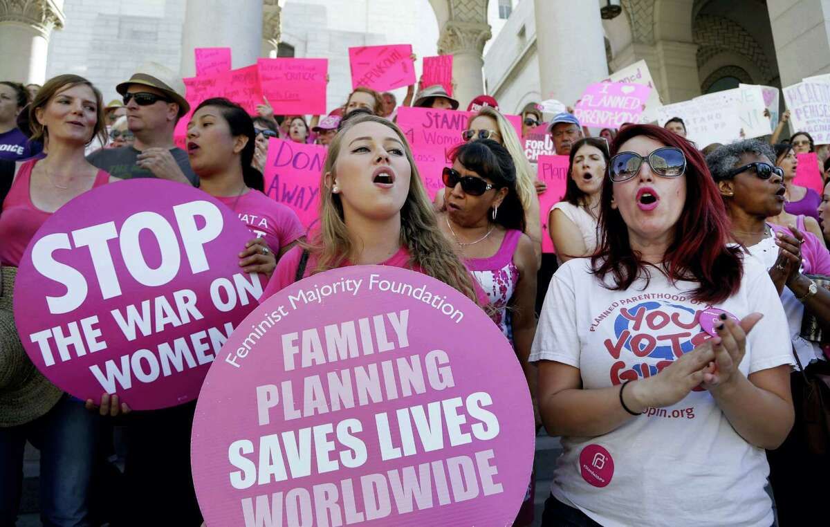"""In this Sept. 9, 2015 photo, Planned Parenthood supporters rally for women's access to reproductive health care on """"National Pink Out Day'' at Los Angeles City Hall. One of President-elect Donald Trump's first, and defining, acts next year could come on Republican legislation to cut off taxpayer money from Planned Parenthood."""