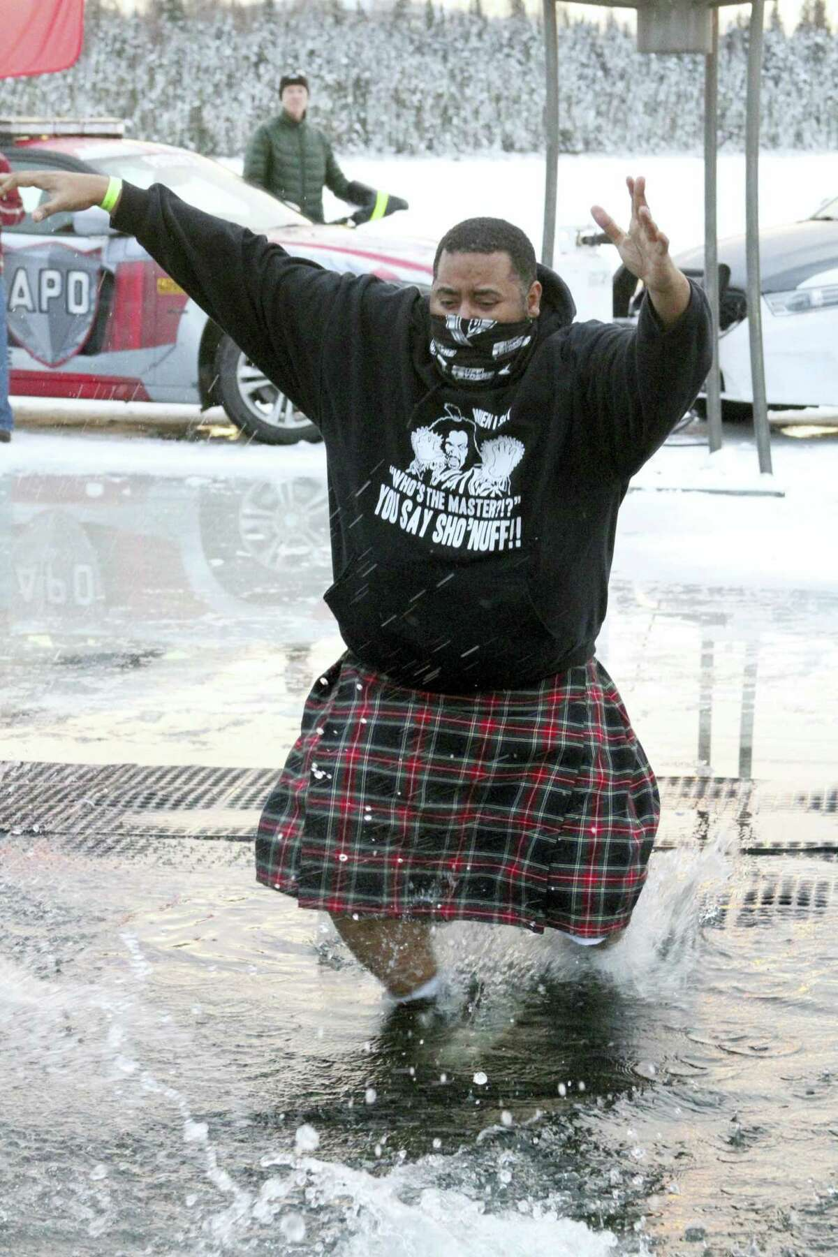 Maceo Garcia takes part in a polar plunge fundraiser at Goose Lake Saturday, Dec. 17, 2016, in Anchorage, Alaska. The plunge was a benefit for Special Olympics Alaska, and has raised more than $2 million for the organization in the eight years it has been held. (AP Photo/Mark Thiessen)