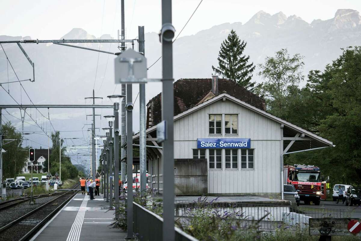 Emergency services attend the scene at Salez - Sennwald train station after a man attacked other passengers aboard a train at Salez, Switzerland, on Saturday, Aug. 13, 2016. Police in Switzerland say a Swiss man set a fire and stabbed people on a train in the country's northeast, wounding six people some seriously, and injuring himself.