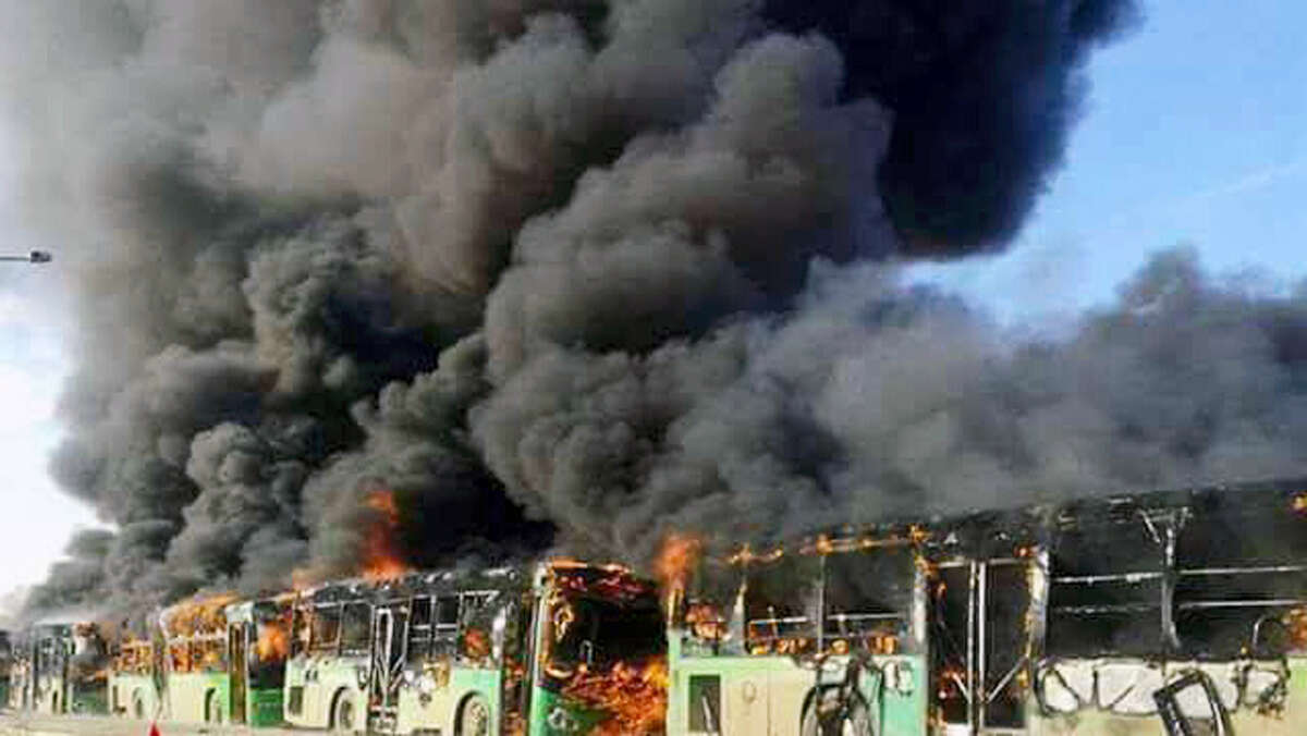 In this photo released by the Syrian official news agency SANA, smoke rises in green government buses, in Idlib province, Syria on Dec. 18, 2016. Activists said militants have burned at least five buses assigned to evacuate wounded and sick people from two villages in northern Syria. The incident could scuttle a wider deal that encompasses the evacuation of thousands of trapped rebel fighters and civilians from the last opposition foothold in east Aleppo.