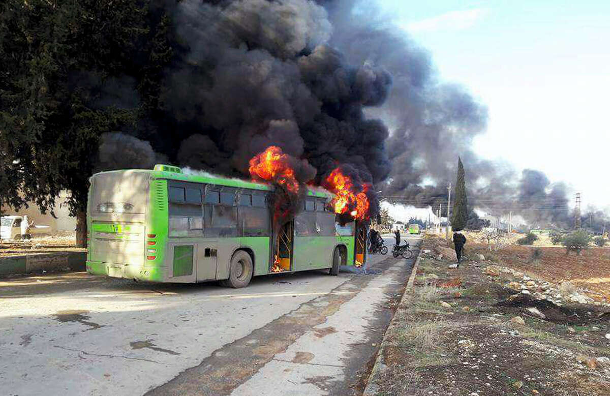 In this photo released by the Syrian official news agency SANA, smoke rises in green government buses, in Idlib province, Syria Dec. 18, 2016. Activists said militants have burned at least five buses assigned to evacuate wounded and sick people from two villages in northern Syria. The incident could scuttle a wider deal that encompasses the evacuation of thousands of trapped rebel fighters and civilians from the last opposition foothold in east Aleppo.