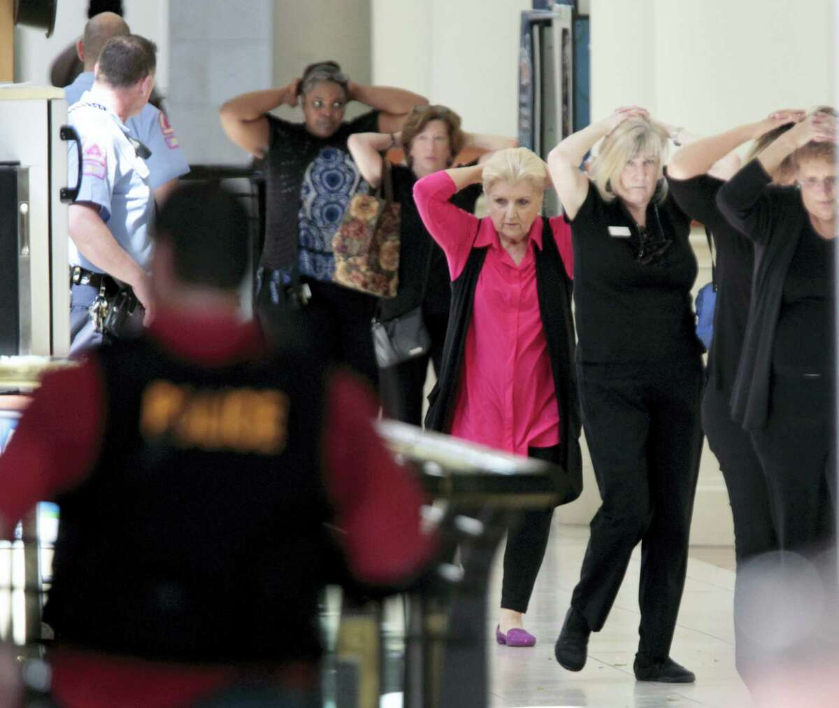 Mall workers and visitors exit to safety through the upper floor food court at Crabtree Valley Mall with hands on their heads as the mall is evacuated in Raleigh, N.C., Saturday, Aug. 13, 2016. Raleigh's police chief says investigators are still trying to determine whether there was a shooting at the Raleigh mall where witnesses reported hearing gunfire.