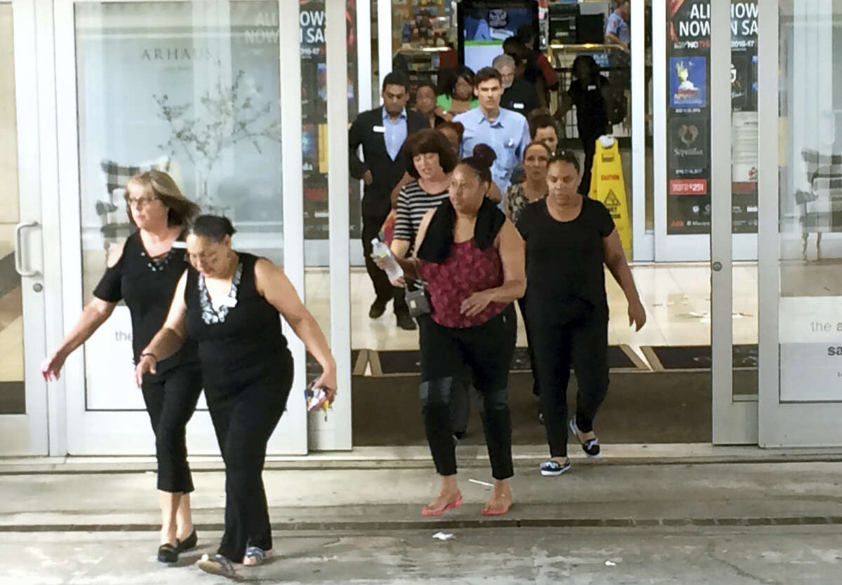 People rush from one of the exits of Crabtree Valley Mall in Raleigh, N.C. Saturday, Aug. 13, 2016. Reports of gunshots inside the busy North Carolina mall caused chaos Saturday afternoon as shoppers ran screaming for the doors or sheltered in stores while dozens of officers arrived on the scene, witnesses said. (Harry Lynch/The News & Observer via AP)