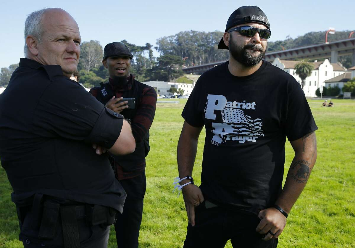 Joey Gibson, right, chats with an official at Crissy Field following the cancellation of the Patriot Prayer event on Saturday, Aug. 26, 2017, in San Francisco, Calif.