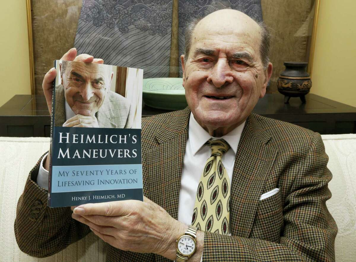 Dr. Henry Heimlich holds his memoir prior to being interviewed at his home in Cincinnati in 2014. Heimlich, the surgeon who created the life-saving Heimlich maneuver for choking victims has died Saturday, Dec. 17, 2016, at Christ Hospital in Cincinnati. He was 96.