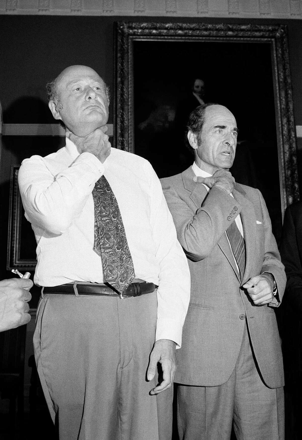 Dr. Henry Heimlich, right, and Mayor Edward Koch demonstrate how a chocking victim should signal for help at New York's City Hall during Heimlich's discussion of his Heimlich Maneuver.