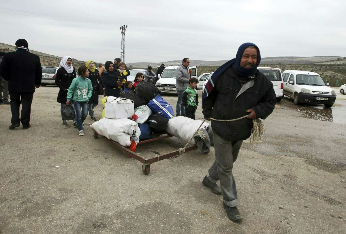 A Syrian man pulls their belongings after he was evacuated with his family from Aleppo, near Idlib, Syria, Friday, Dec. 16, 2016. Turkey's Foreign Minister Mevlut Cavusoglu says 7,500 civilians have been evacuated from the Syrian city of Aleppo and that he has reached out to Tehran in a bid to keep the process on track.