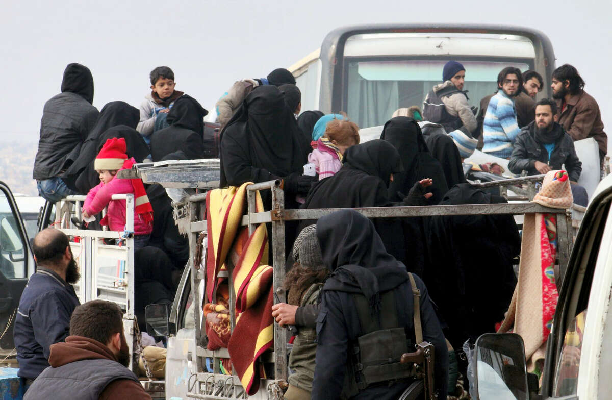 This image released by Aleppo 24, shows residents of eastern Aleppo arriving in western rural Aleppo, Syria, Friday, Dec. 16, 2016, as part of an evacuation deal. The evacuation of eastern Aleppo stalled Friday after an eruption of gunfire, as the Syrian government and rebels threw accusations at each other, raising fears that a peaceful surrender of the opposition enclave could fall apart with thousands of people believed to be still inside. (Aleppo 24 via AP)