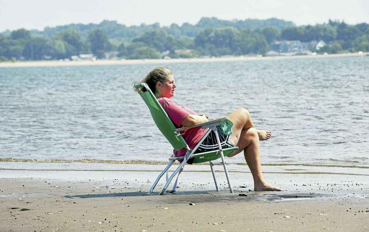 Karen Bryan of Massachusetts sits on a sandbar during low tide at Silver Sands Beach in Milford while visiting family on 8/12/2016.