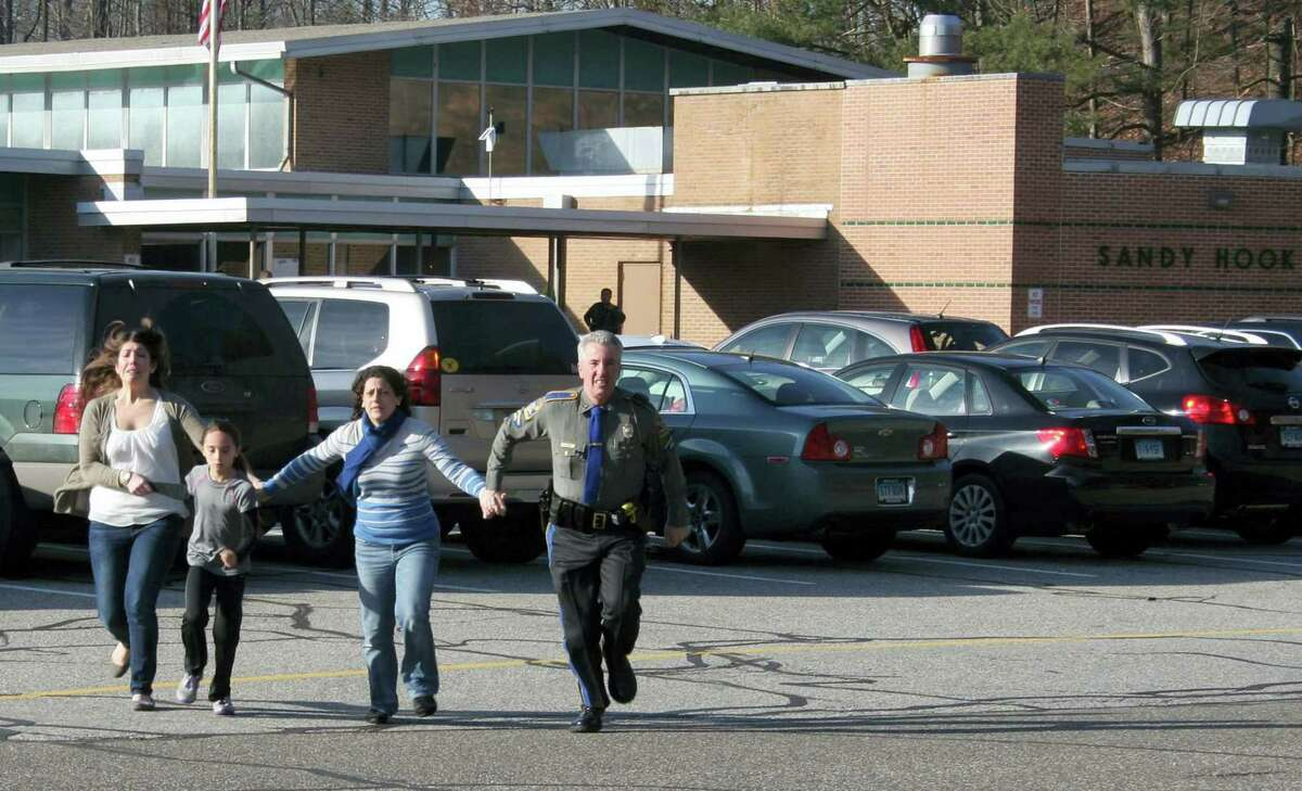 In this Friday, Dec. 14, 2012, file photo provided by the Newtown Bee, a police officer leads two women and a child from Sandy Hook Elementary School in Newtown where a gunman opened fire.