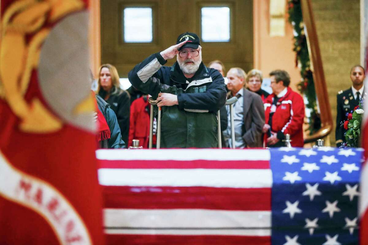 A mourner salutes the casket of John Glenn as he lies in honor, Friday, Dec. 16, 2016, in Columbus, Ohio. Glenn's home state and the nation began saying goodbye to the famed astronaut who died last week at the age of 95. John Minchillo — AP Photo