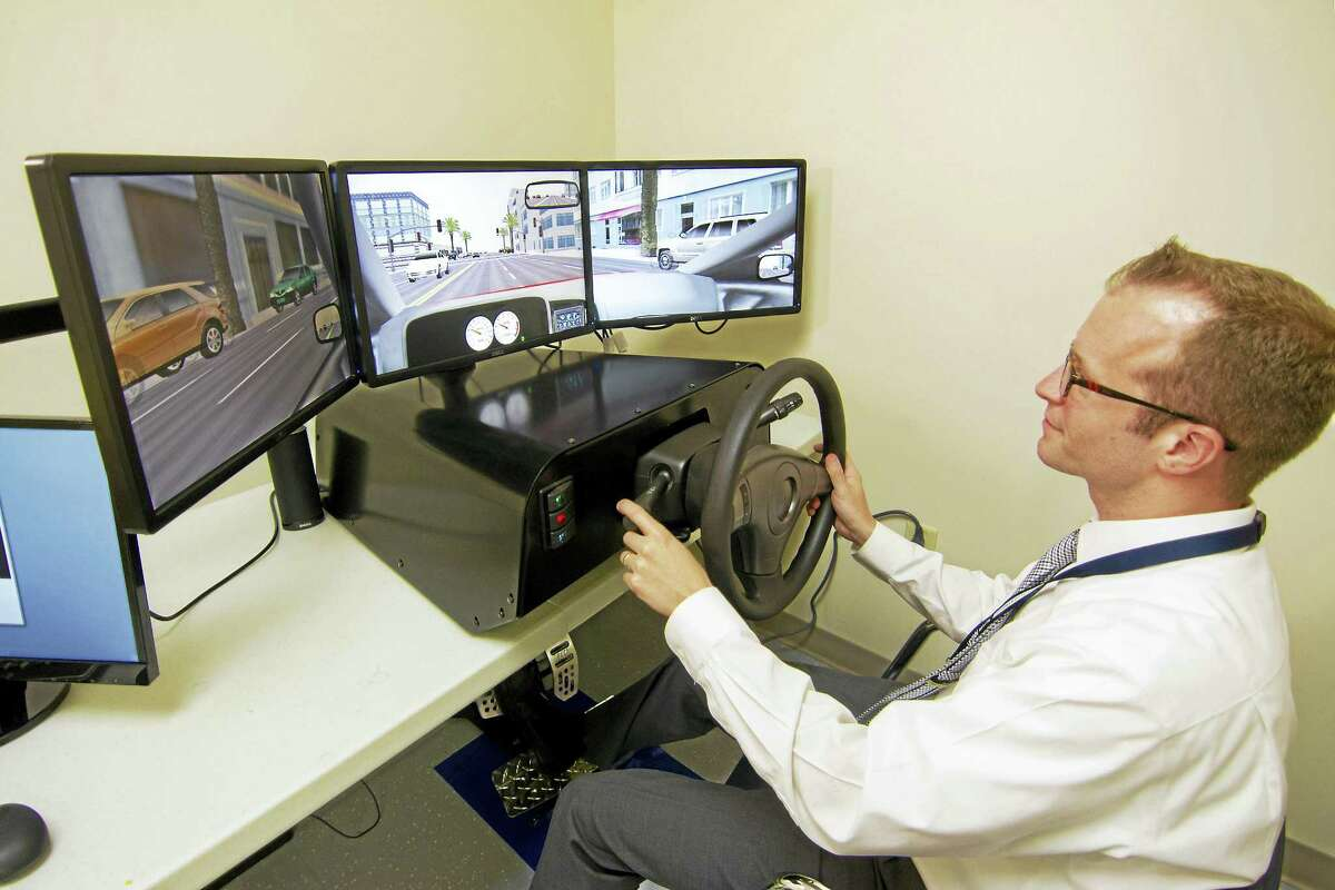 Dr. Kevin Manning at the UConn Health Center on Aging demonstrates the driving simulator for testing elderly adults.Tony Bacewicz - Conn. Health I-Team