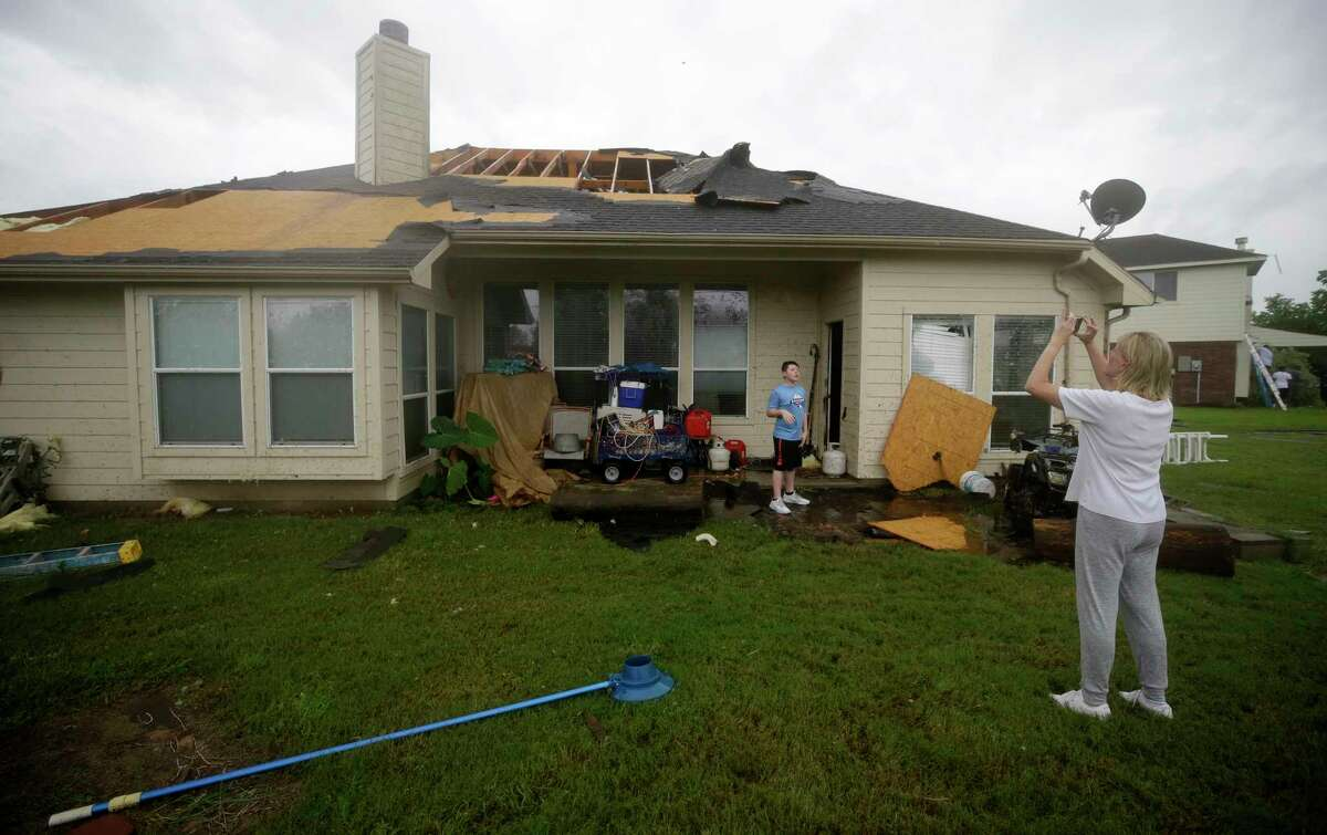 A homeowner takes a photo outside her home after a tornado hit in the Lone Oak subdivision Saturday, Aug. 26, 2017, in Cypress. Several tornadoes from Hurricane Harvey have been reported in the area.