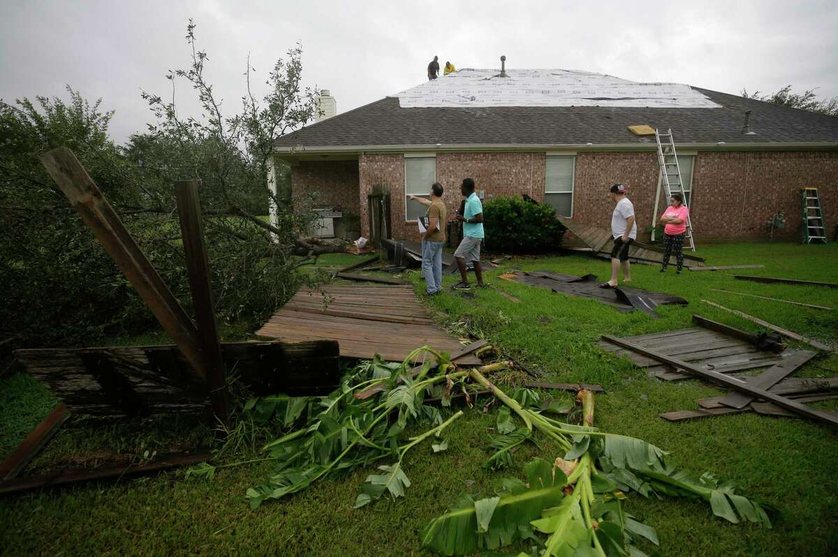 People look at tornado damage from Hurricane Harvey in the Lone Oak subdivision Saturday, Aug. 26, 2017, in Cypress.