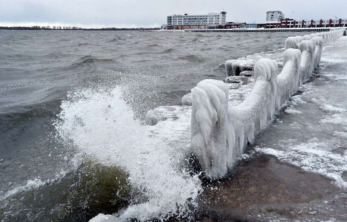 Waves crash along frozen abutments and fencing Thursday, Dec. 15, 2016 on Presque Isle Bay in Erie, Pa. Much of the northern Mid-Atlantic and Northeast will stay cold for the next couple of days as the arctic air remains stuck over the northern Appalachians, the National Weather Service said.